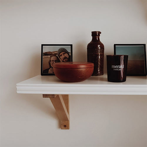 minimalistic decor - a shelf with two photos and some homewares