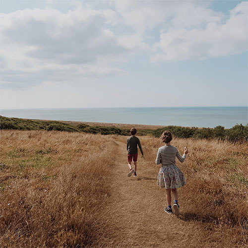 two kids running in the dunes with sea in the background