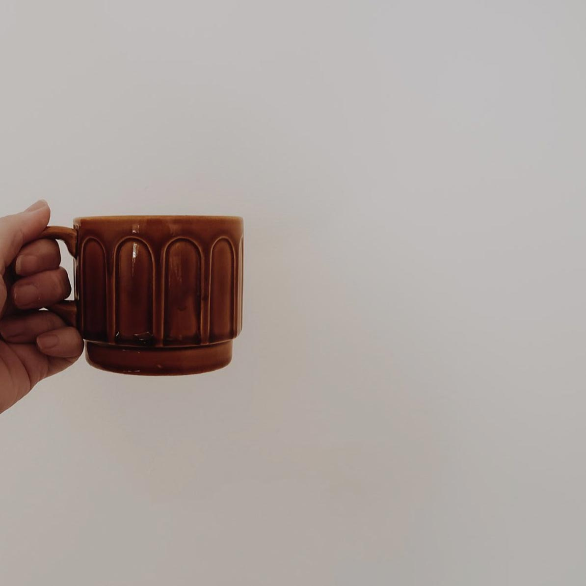a hand holding a brown cup of tea
