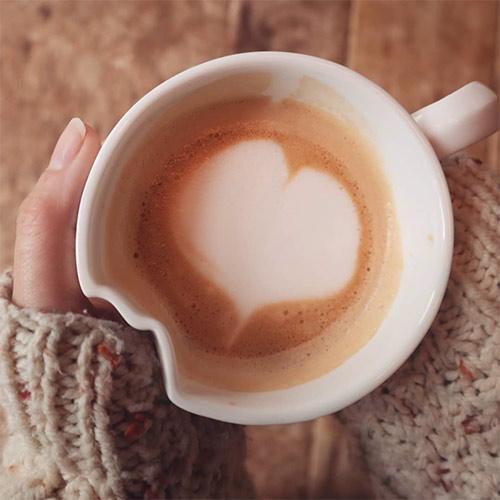 a cup of coffee with a little milk foam heart in it