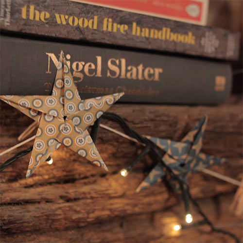 fairy light and star garland in front of a pile of books