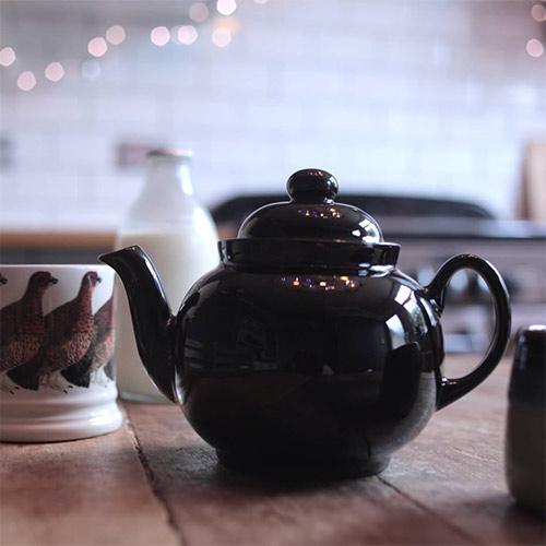 a teapot, mugs and milk on a kitchen table