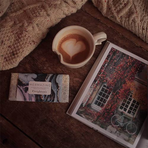 cup of coffee, a magazine and knitwear on a table