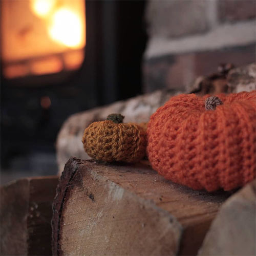 knitted pumpkins in front of a wood fire
