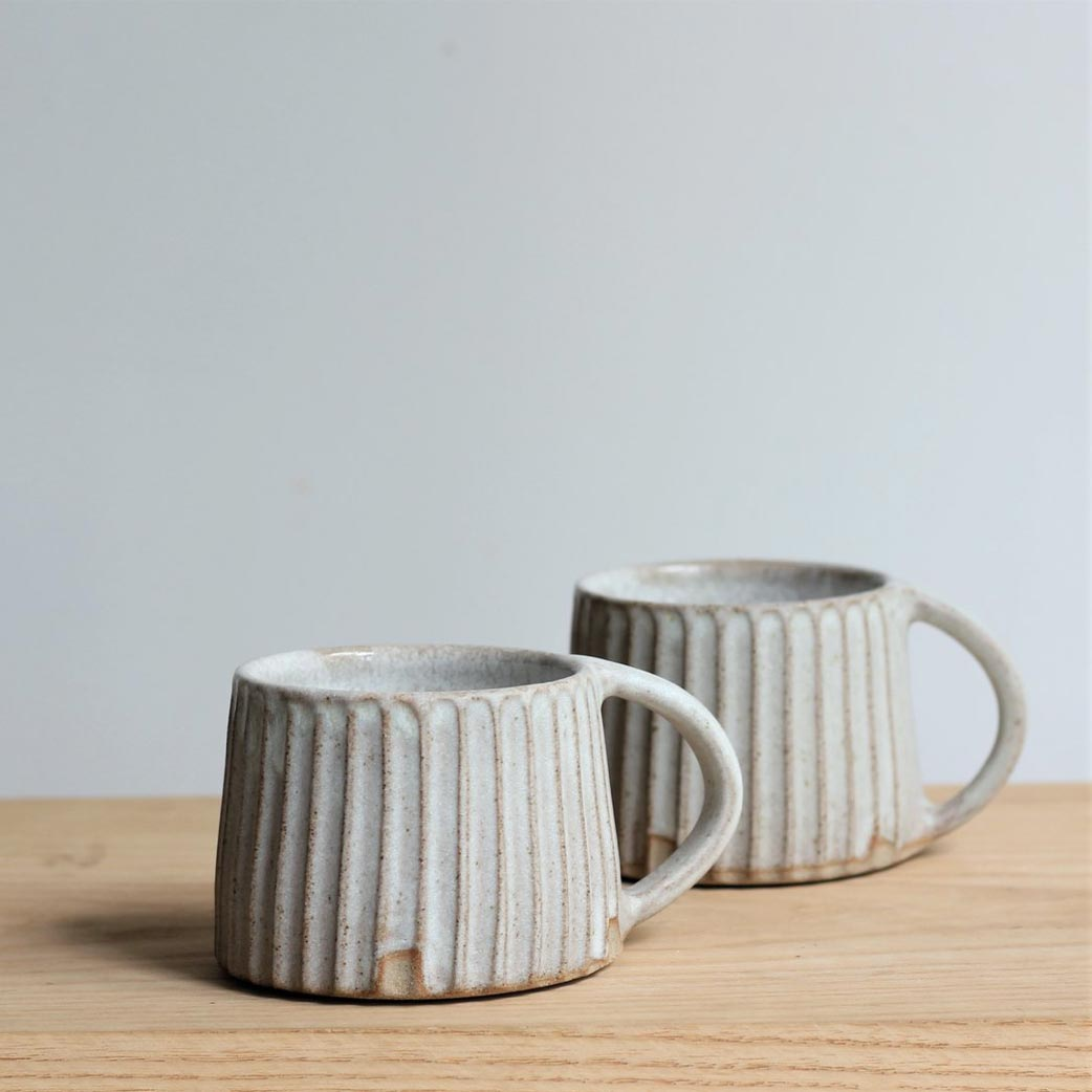 two carved mugs on a table