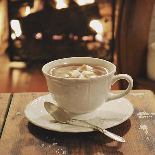 a cup of hot chocolate on a table in front of a fireplace