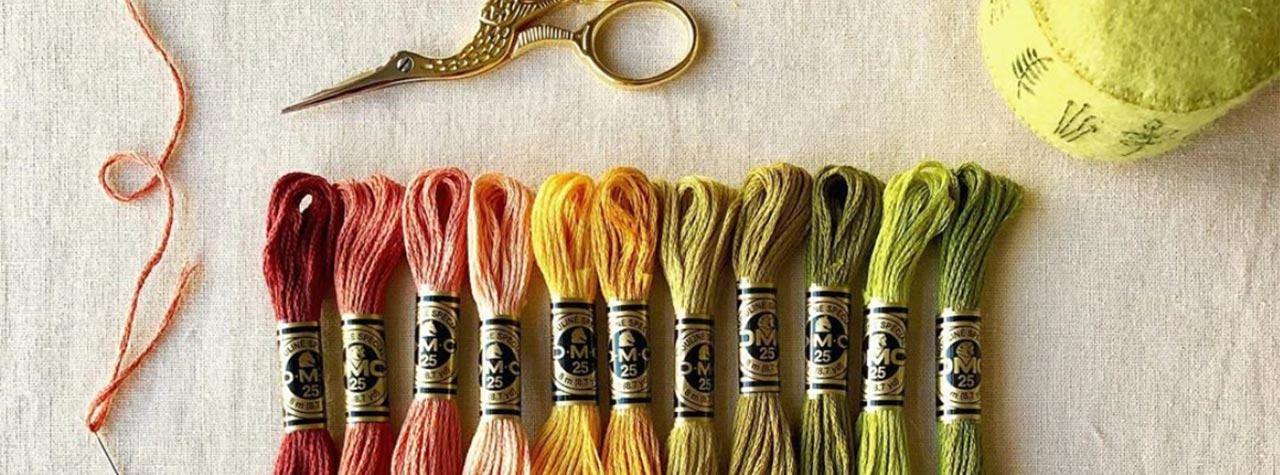 different colours of embroidery threads, a scissor and needle