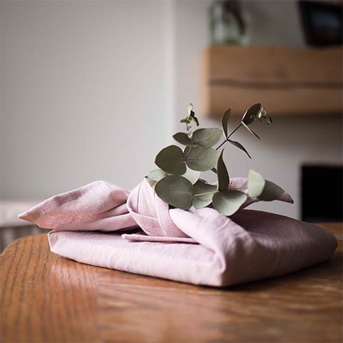 a present wrapped in linen cloth on a table