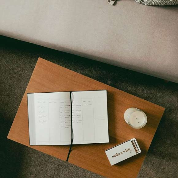 a journal, candles and matches on a brown table next to a couch