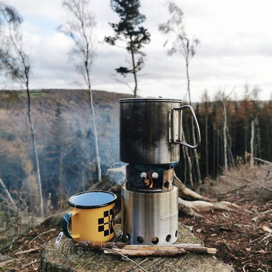 outdoor picnic with a gas burner, kettle and enamel mug