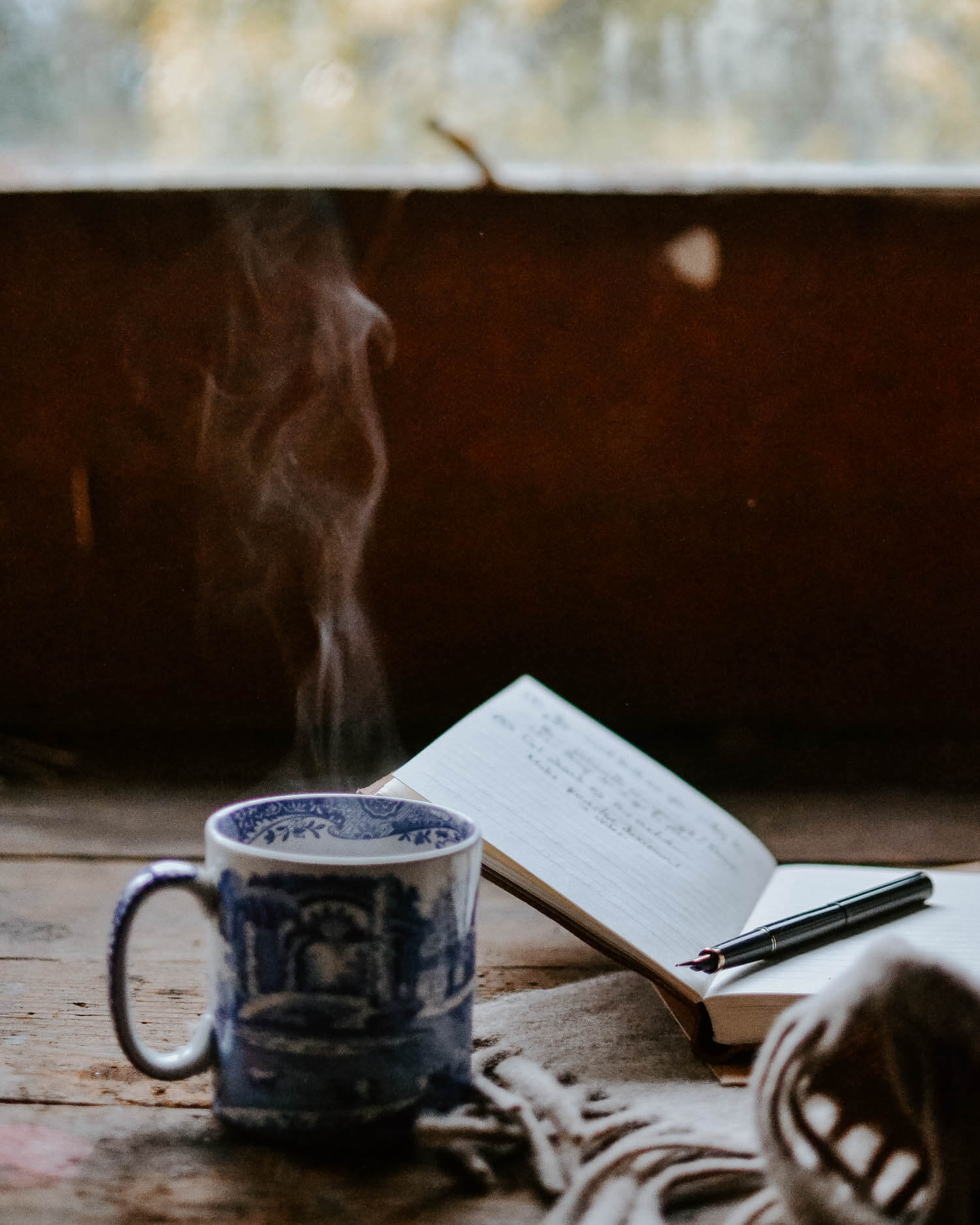 a steaming cup of tea with a notebook and pen