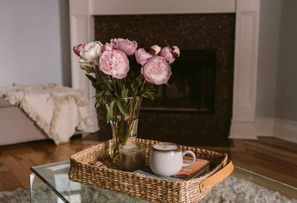 a table with a vase with flowers, a tray with a cup of coffee, a fireplace in the background