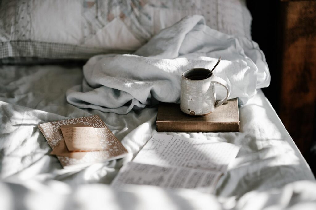 a bed with several journals, a book and a cup of tea