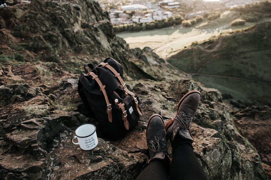 a backpacker resting in the hills with a cup of tea