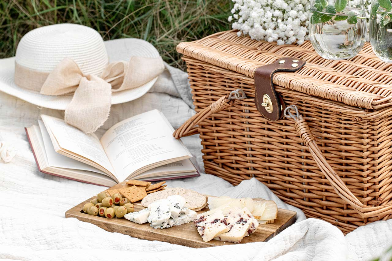 picnic basket and cheese board on a blanket