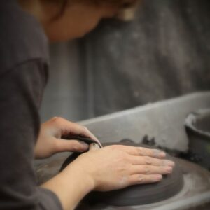woman making a handmade product from clay