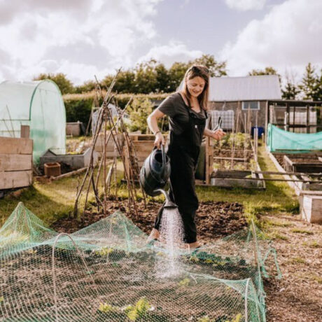 Fiona Barrows watering the plants in her allotment