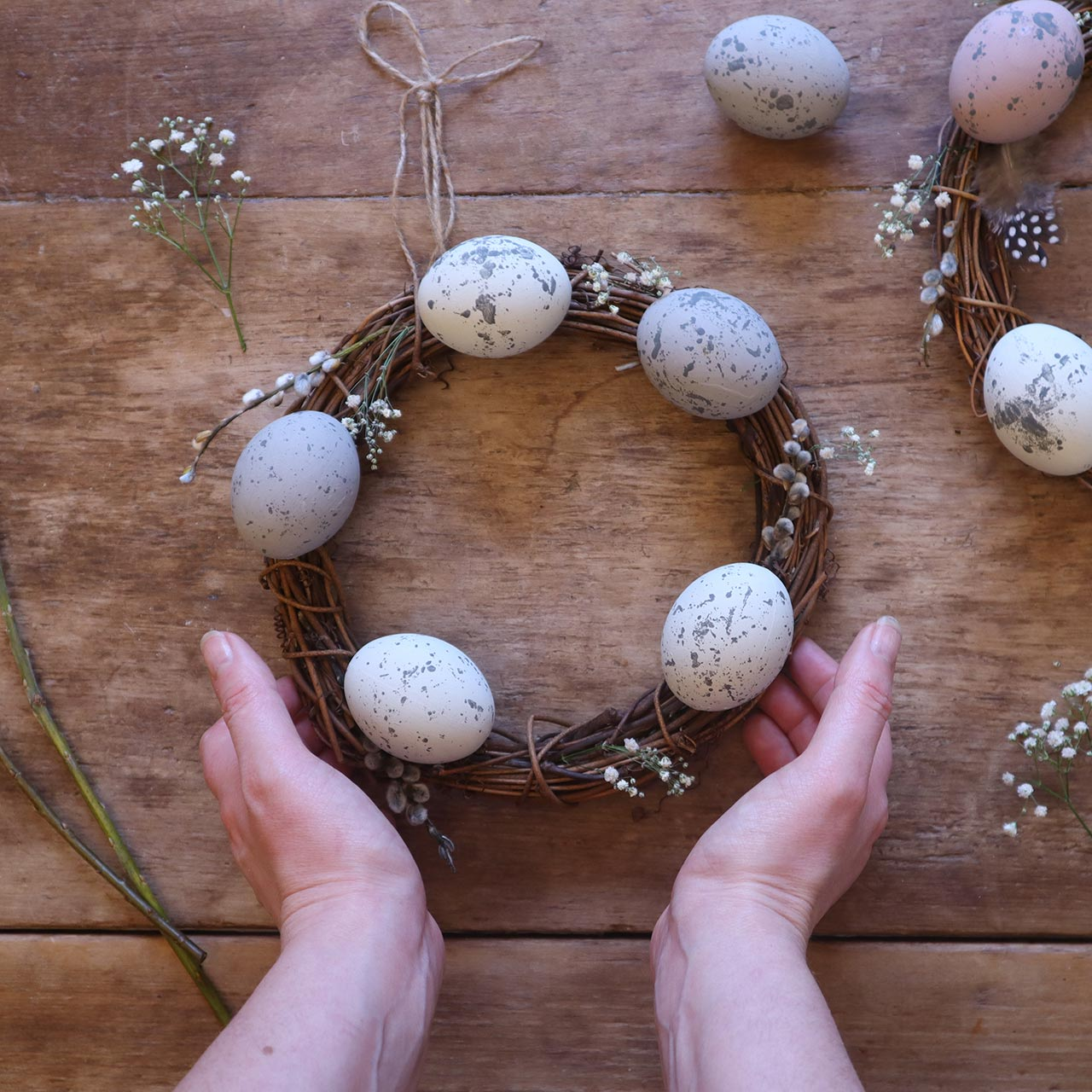 two hands holding a spring wreath made from twigs, flowers and eggs - a spring guide to hygge