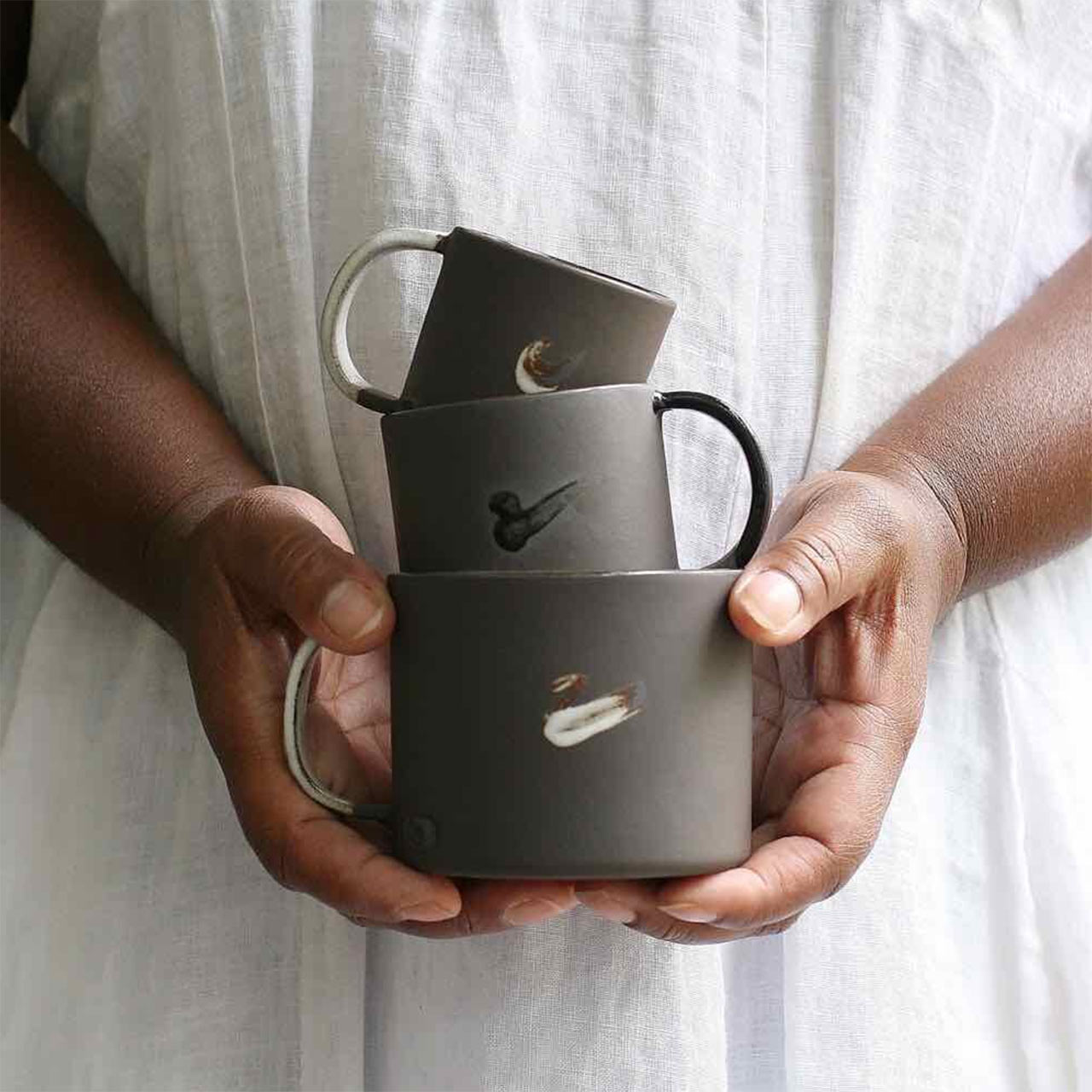 two hands holding 3 different sizes of mugs from naked clay ceramics