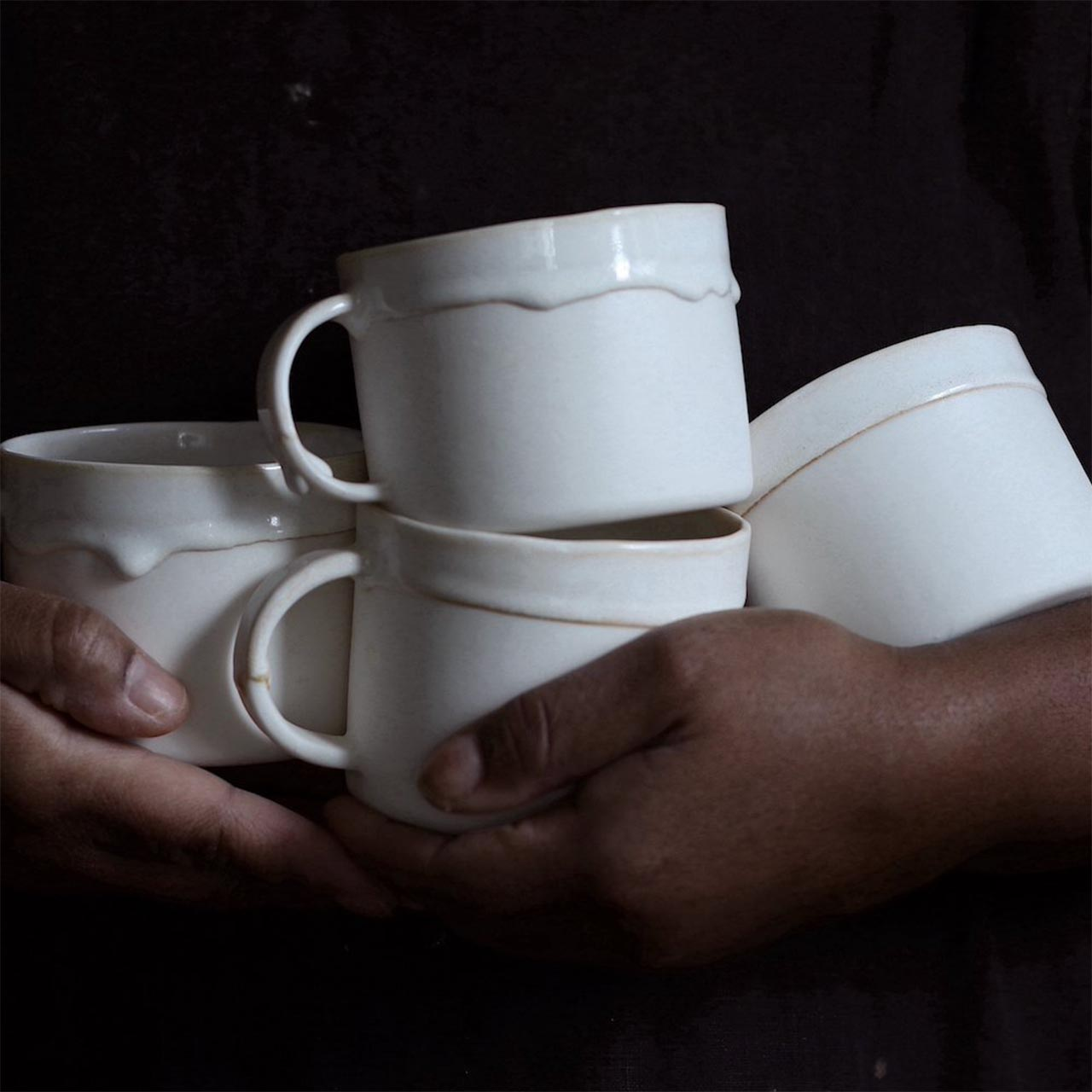 two hands holding 4 white ceramic mugs from naked clay ceramics