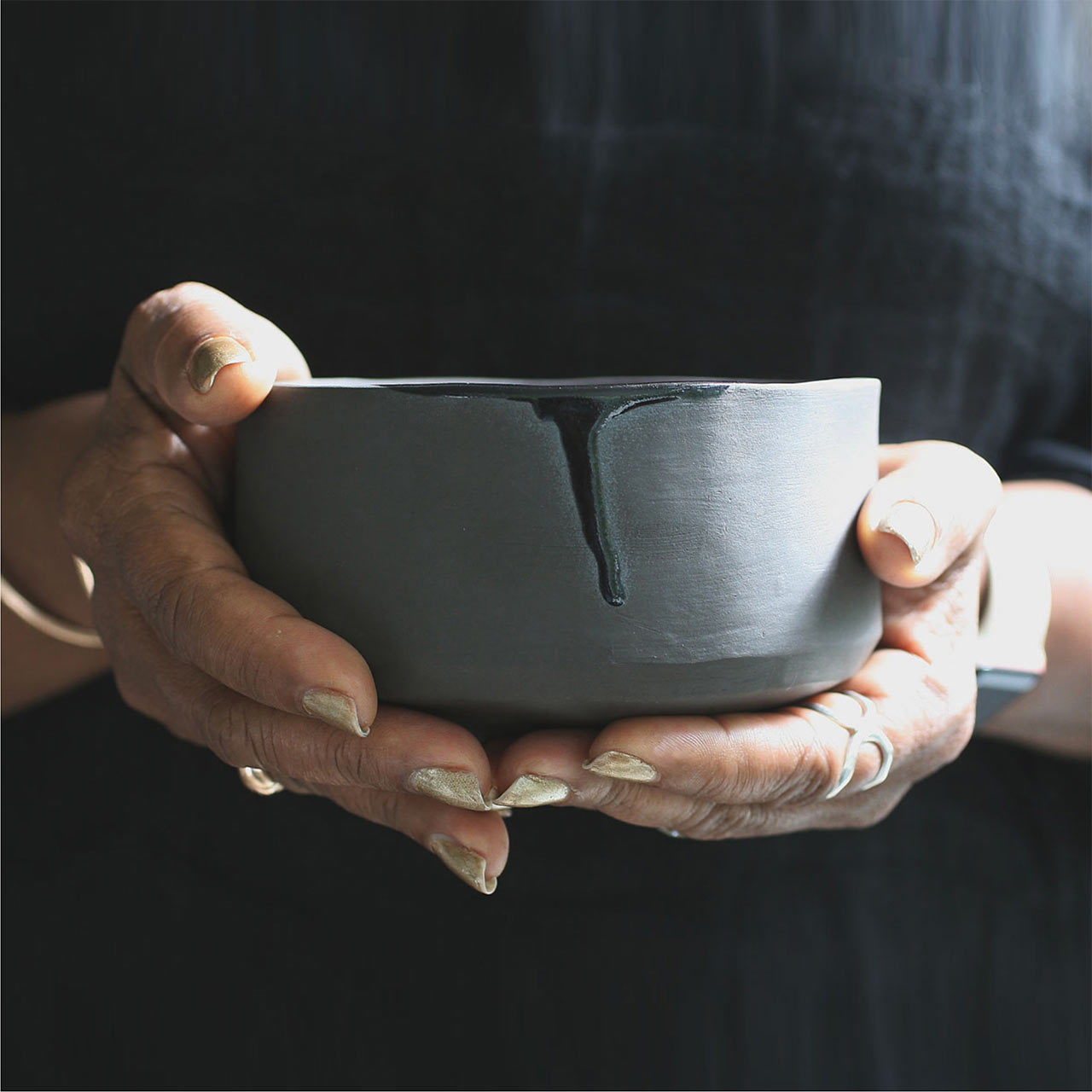 two hands holding a blue ceramic bowl from naked clay ceramics