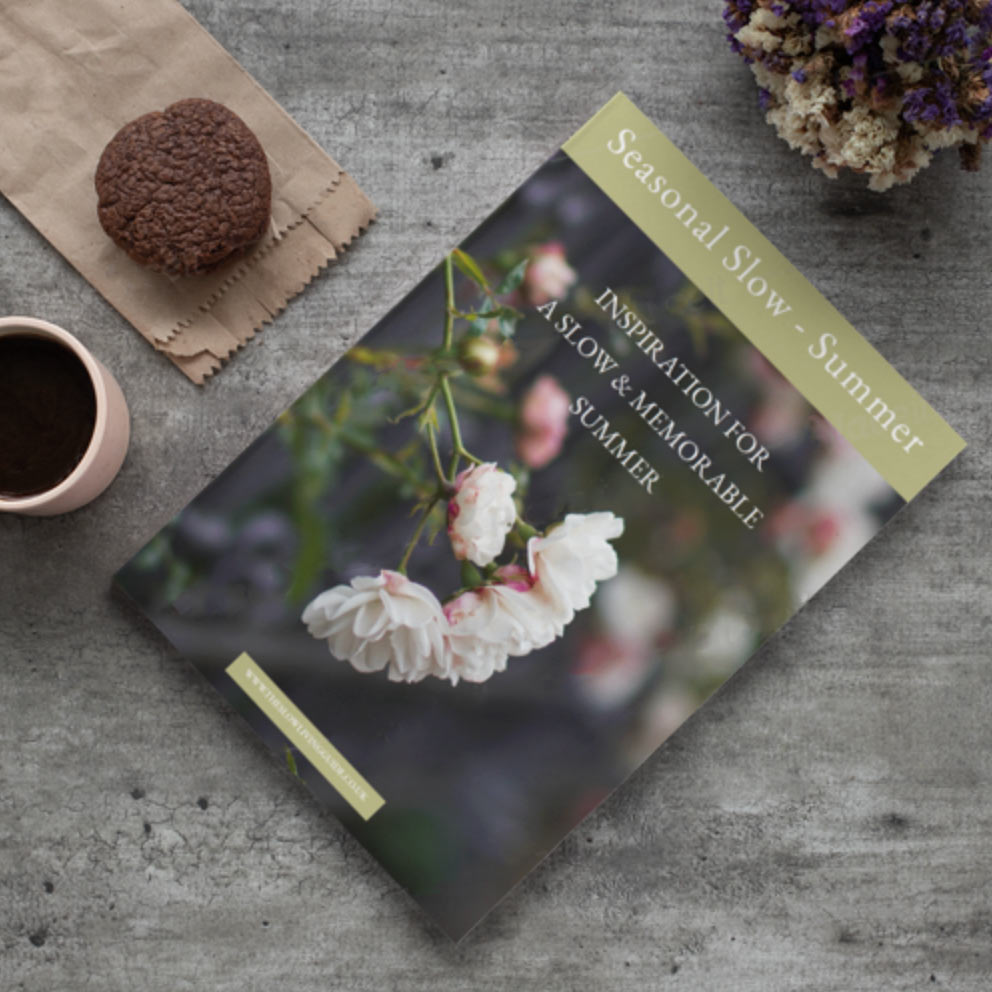 a copy of seasonal slow summer lying on a wooden table with a cup of coffee and a muffin next to it