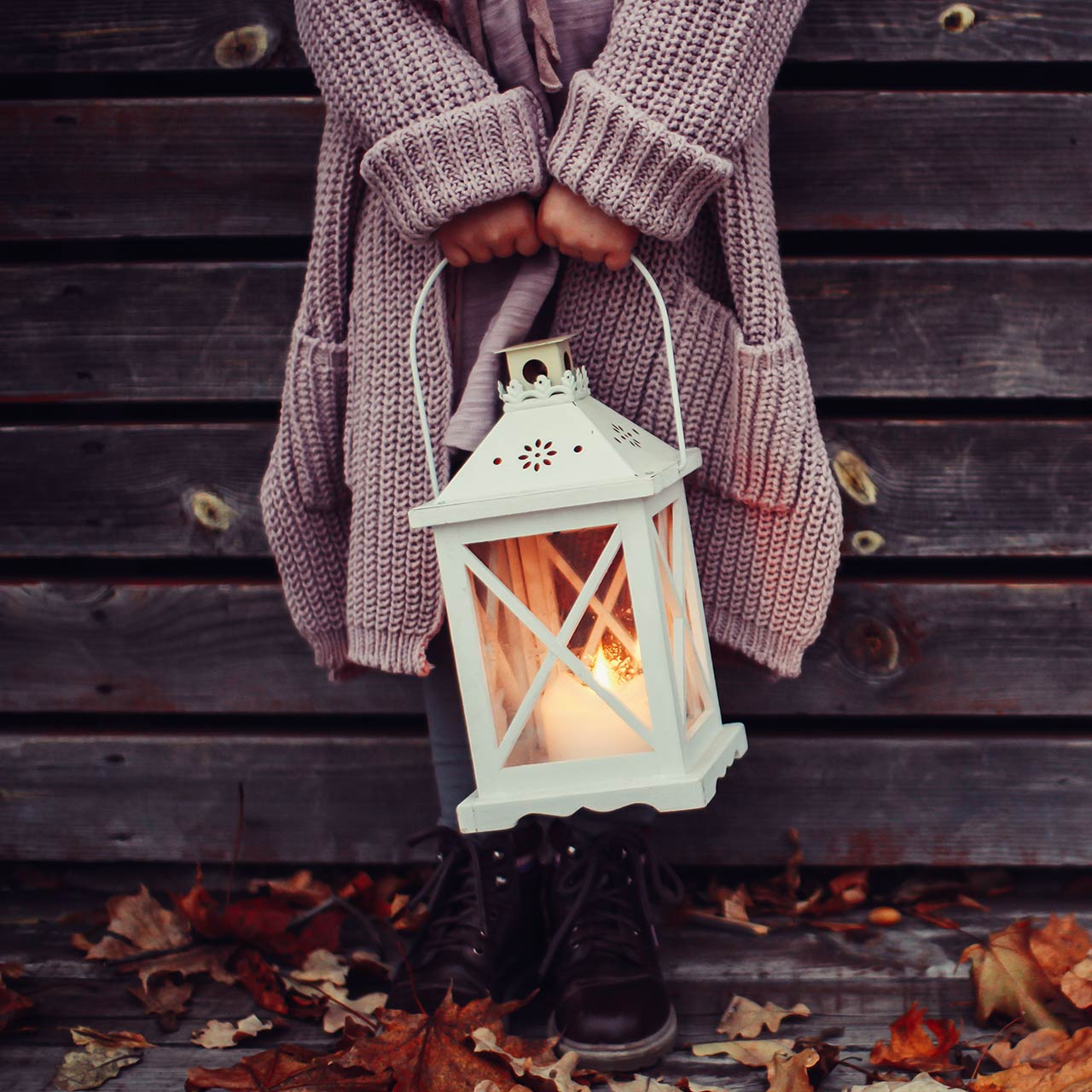girl standing in front of a wooden home wearing a vintage pink oversized wool jumper and holding a white lantern with a burning candle