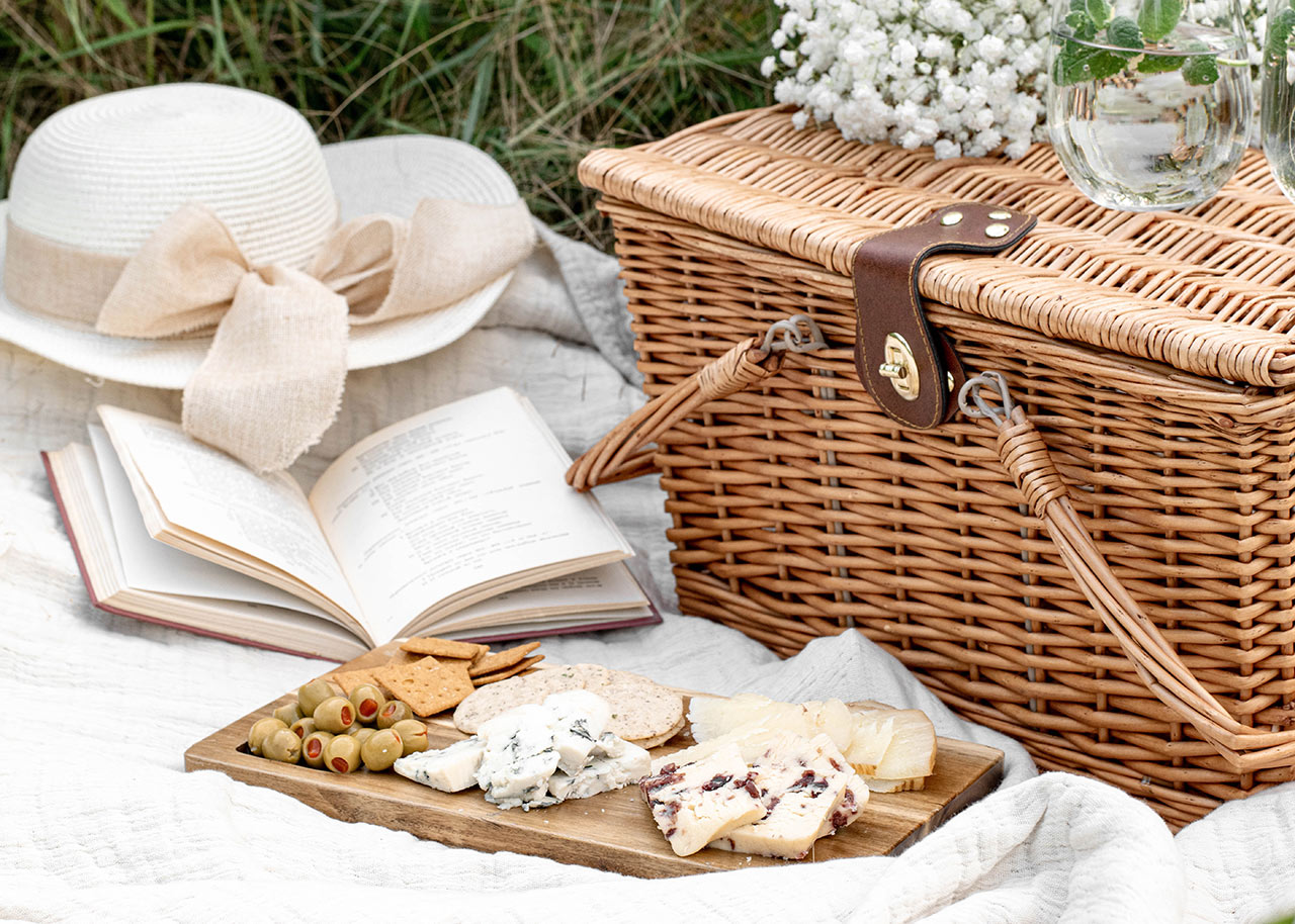 a blanket with a picnic hamper, food, flowers, a book and a sun hat