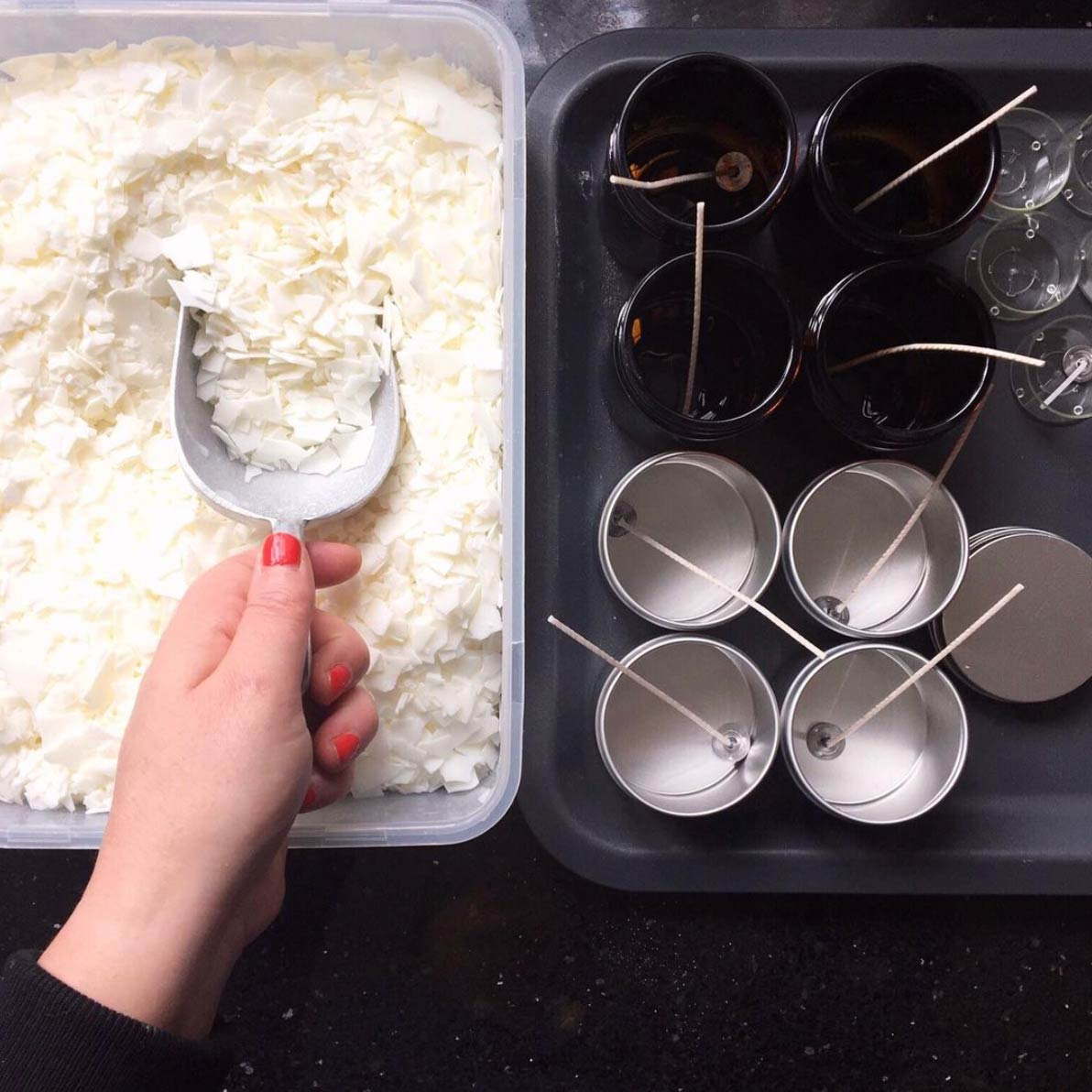 a woman's hand scooping soy flakes to melt