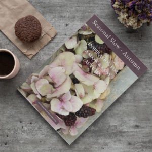 mock up of seasonal slow autumn inspiration magazine lying on a table with cup of coffee and muffing next to it