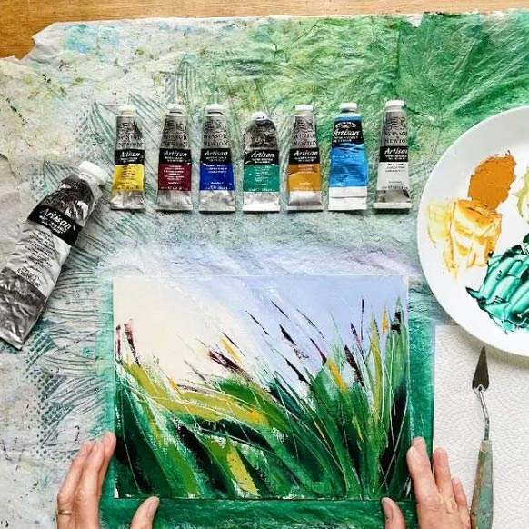 flatlay of a small nature-inspired painting with tubes of paint and a mixing plate laying next to it