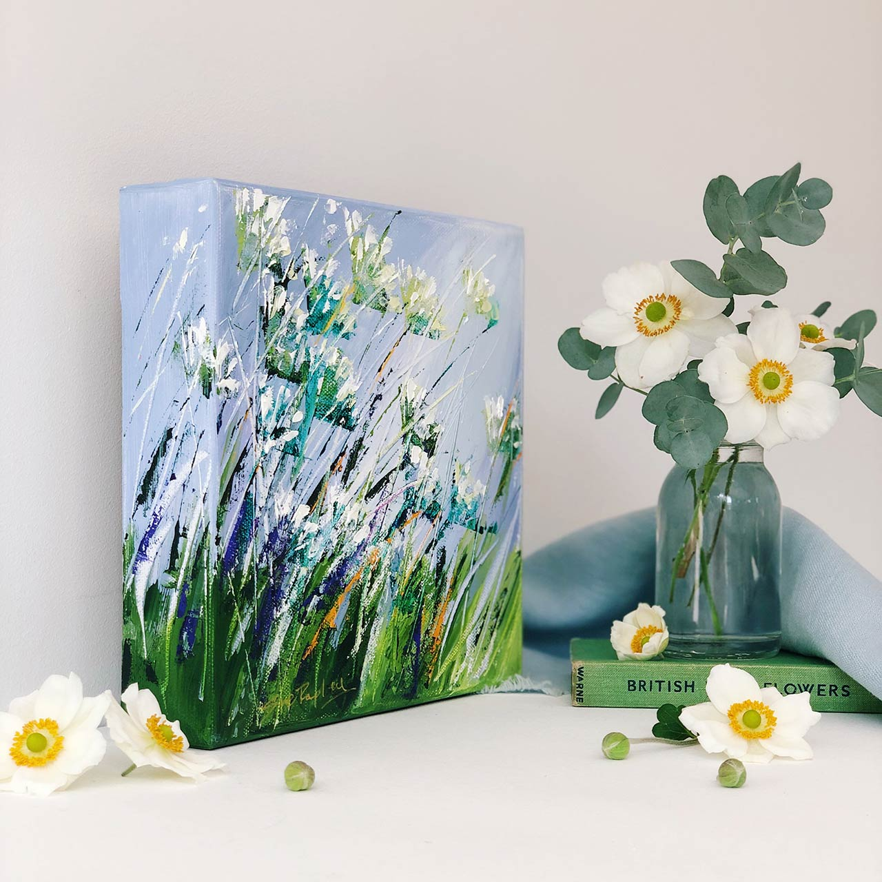 small floral painting standing against a wall, a vase with flowers next to it and a copy of British wildflowers