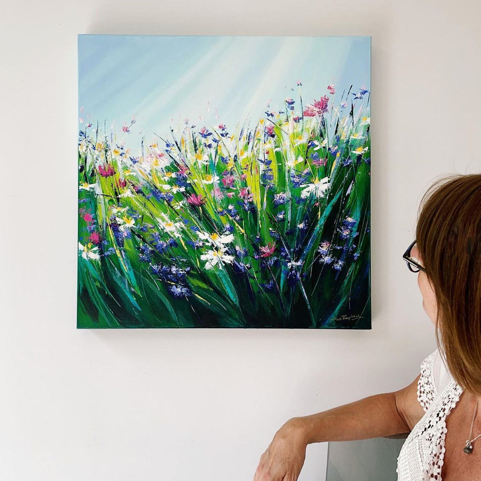 sue Rapley watching one of her paintings on the wall