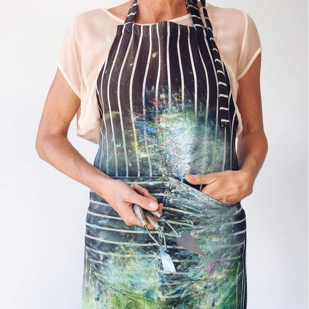 torso of Sue Rapley dressed in a painter's apron and holding painting tools
